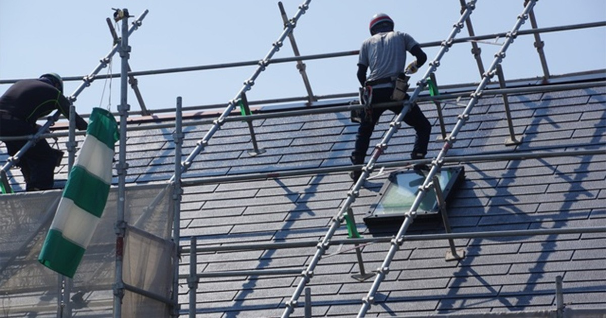 屋根塗装工事している職人